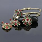 Bronze set plated with yellow gold with emerald and coral